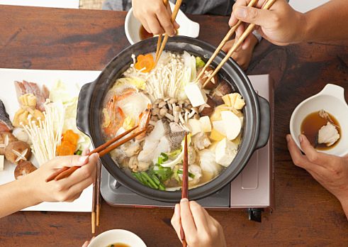 Parents and children eating Japanese nabe