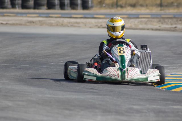 Karting - driver in helmet driving on kart circuit