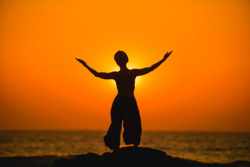 51786420 - female meditates during yoga and opens her body to the sun at a sunset